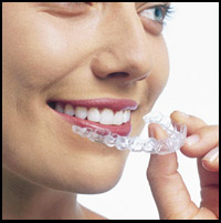 A woman smiling while holding her new invisalign.